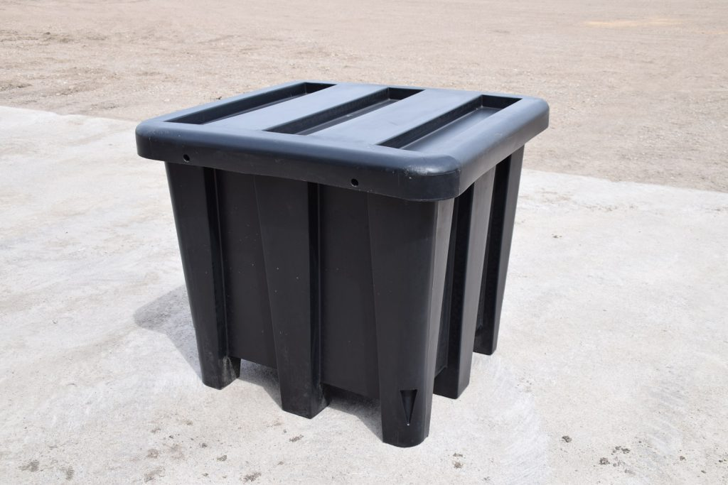 black plastic tote container sitting on cement