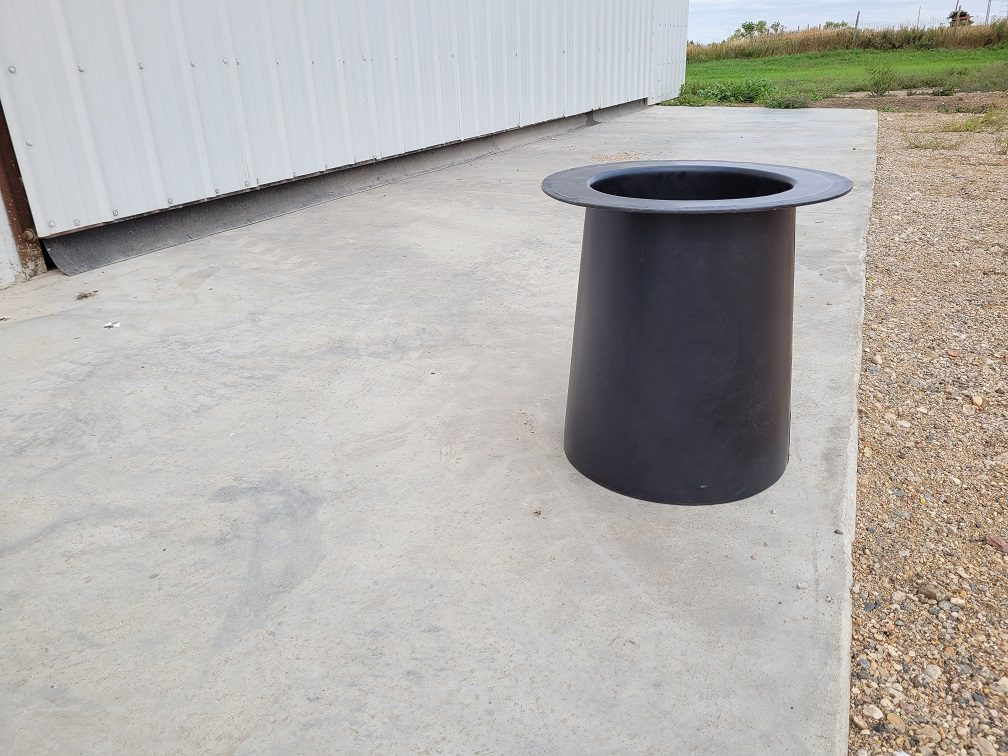 black plastic drink tube sitting on cement in front of shop